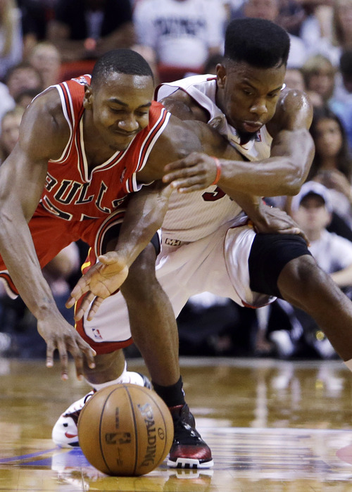 Chicago Bulls guard Marquis Teague, left, and Miami Heat guard Norris Cole battle for a loose ball during the first half of Game 1 of the NBA basketball playoff series in the Eastern Conference semifinals, Monday, May 6, 2013 in Miami. (AP Photo/Lynne Sladky)
