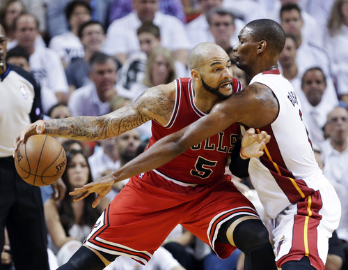 Chicago Bulls forward Carlos Boozer (5) drives against Miami Heat center Chris Bosh during the first half of Game 1 of the NBA basketball playoff series in the Eastern Conference semifinals, Monday, May 6, 2013 in Miami. (AP Photo/Lynne Sladky)