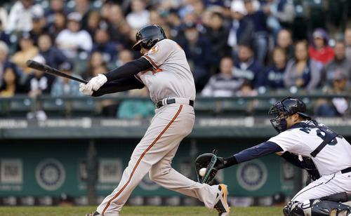 Baltimore Orioles' Manny Machado strikes out swinging as Seattle Mariners' Jesus Montero catches the pitch in the first inning of a baseball game Wednesday, May 1, 2013, in Seattle. (AP Photo/Elaine Thompson)