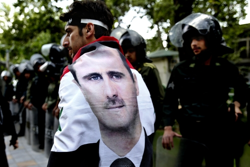 An Syrian man wrapped in a Syrian flag with a portrait of President Bashar Assad, walks past anti riot police during an anti-Israeli demonstration in front of the UN office in Tehran, Iran, Monday, May 6, 2013. Iran Condemns Israeli Air strikes on Syria and urged countries in the region to stand against the attack. (AP Photo/Ebrahim Noroozi)