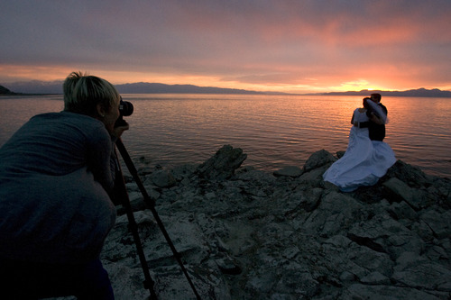 Rick Egan  | The Salt Lake Tribune   Susan Adams takes advantage of the sunset, as she shoots wedding photos of Emily Mecham, Brian Shaw, Provo, at the Great Salt Lake, Monday, May 6, 2013.