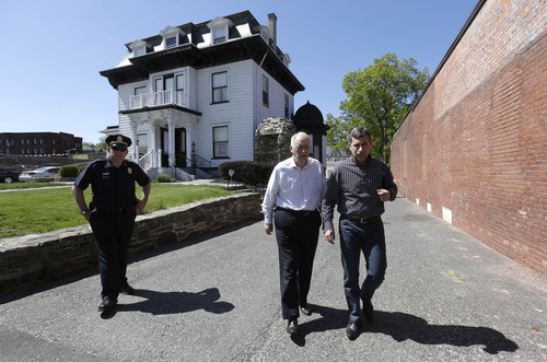 Ruslan Tsarni, right, uncle of killed Boston Marathon bombing suspect Tamerlan Tsarnaev, approaches members of the media, not shown, in front of the Graham, Putnam, and Mahoney Funeral Parlors, in Worcester, Mass., as funeral director and owner Peter Stefan, center, walks with him Sunday, May 5, 2013. Stefan has pleaded for government officials to use their influence to convince a cemetery to bury Tsarnaev, but so far no state or federal authorities have stepped forward. (AP Photo/Steven Senne)