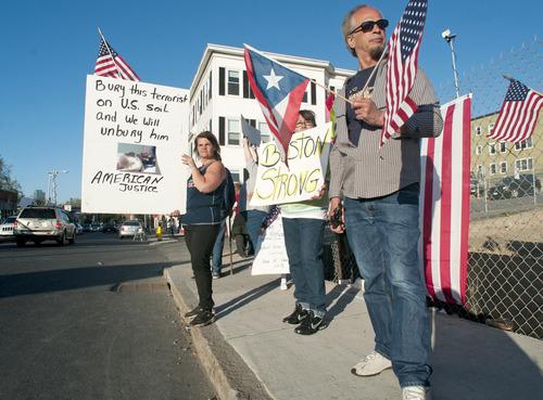 From left, Lisa Taurasi, Lucy Rodriguez and Luis Barbosa, all of Worcester, Mass., hold protest signs as they stand across the street from Graham Putnam & Mahoney Funeral Parlors in Worcester, Mass. on Sunday evening, May 5, 2013.  They are upset about the possibility that Boston marathon bombing suspect Tamerlan Tsarnaev may be buried in the United States, and that the body is being held at Graham Putnam & Mahoney Funeral Parlors while a search for a cemetery willing to bury him continues. (AP Photo/Worcester Telegram & Gazette, Betty Jenewin)