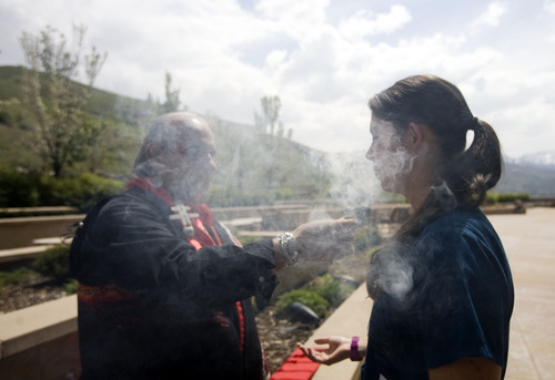 """Kim Raff     The Salt Lake Tribune (right) Nickole (cq) Canfield, a health care assistant, participates in a smudging ceremony by Native American shaman, Lacee Harris during the """"Blessing of the Hands"""" on the outdoor patio of the Huntsman Cancer Institute in Salt Lake City on May 6, 2013. The event gathered a diverse group of spiritual care providers to bless hospital caregivers, employees and patrons."""
