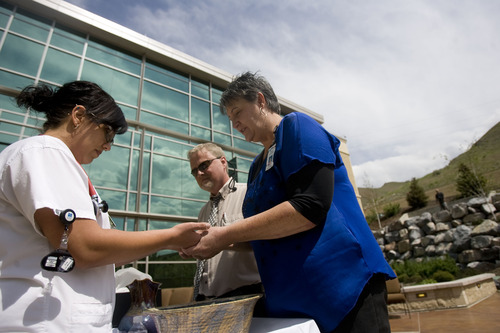 """Kim Raff     The Salt Lake Tribune (left) Melanie Chavez, a registered nurse, bows her head as she is blessed by (middle) Wes Wilde, a chaplain from Summit Home Health, and (right) Irene Huntsman, a spiritual care volunteer, during the """"Blessing of the Hands"""" on the outdoor patio of the Huntsman Cancer Institute in Salt Lake City on May 6, 2013. The event gathered a diverse group of spiritual care providers to bless hospital caregivers, employees and patrons."""