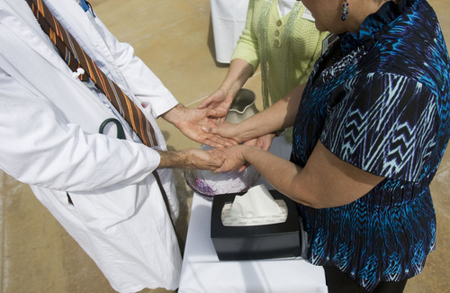"""Kim Raff     The Salt Lake Tribune Dr. G. Weldon Gilcrease has his hands washed and blessed during the """"Blessing of the Hands"""" on the outdoor patio of the Huntsman Cancer Institute in Salt Lake City on May 6, 2013. The event gathered a diverse group of spiritual care providers to bless hospital caregivers, employees and patrons."""