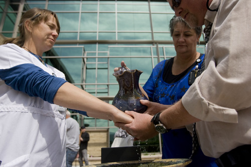 """Kim Raff     The Salt Lake Tribune (left) Jamie Fendler, a registered nurse, has her hands blessed by (right) Wes Wilde, a chaplain from Summit Home Health, and (middle)  Irene Huntsman, a spiritual care volunteer, during the """"Blessing of the Hands"""" on the outdoor patio of the Huntsman Cancer Institute in Salt Lake City on May 6, 2013. The event gathered a diverse group of spiritual care providers to bless hospital caregivers, employees and patrons."""