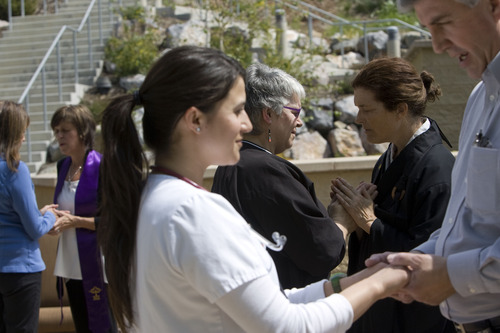 """Kim Raff     The Salt Lake Tribune (center left) Camille Scrip, a registered nurse, is blessed by (center right) Kelly Soon Fogarty, a Buddhist monk, during the """"Blessing of the Hands"""" on the outdoor patio of the Huntsman Cancer Institute in Salt Lake City on May 6, 2013. The event gathered a diverse group of spiritual care providers to bless hospital caregivers, employees  and patrons. """"I can sleep anytime,"""" says Scrip who is currently working the grave yard shift but came in on her time off just to receive the blessings. """"It touched my soul,"""" Scrip says of her experience the previous year."""