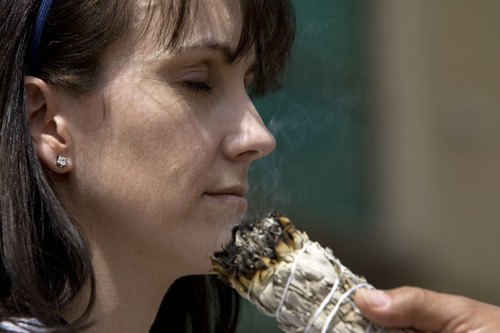 """Kim Raff     The Salt Lake Tribune Melissa Banner, a registered nurse, participates in a smudging ceremony by Native American shaman, Lacee Harris during the """"Blessing of the Hands"""" on the outdoor patio of the Huntsman Cancer Institute in Salt Lake City on May 6, 2013. The event gathered a diverse group of spiritual care providers to bless hospital caregivers, employees  and patrons."""