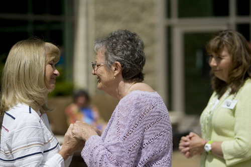 """Kim Raff     The Salt Lake Tribune (middle) Myrna Hirst talks with (left) Janet Blake after giving her a blessing during the """"Blessing of the Hands"""" on the outdoor patio of the Huntsman Cancer Institute in Salt Lake City on May 6, 2013. The event gathered a diverse group of spiritual care providers to bless hospital caregivers, employees  and patrons. """"This is really special,"""" says Blake, whose husband is in the ICU. Blake decided to come out on the patio to enjoy the sun and was pleasantly surprised by the blessing event."""
