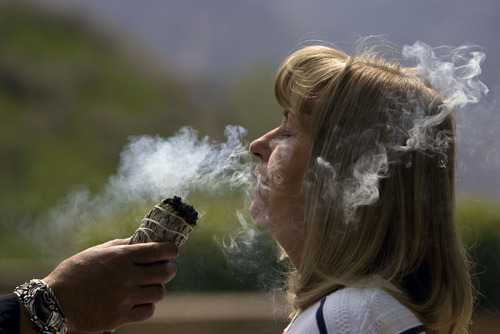 """Kim Raff     The Salt Lake Tribune Janet Blake breaths in smoke during a smudging ceremony by Native American shaman, Lacee Harris during the """"Blessing of the Hands"""" on the outdoor patio of the Huntsman Cancer Institute in Salt Lake City on May 6, 2013. The event gathered a diverse group of spiritual care providers to bless hospital caregivers, employees and patrons. """"This is really special,"""" says Blake, whose husband is in the ICU. Blake decided to come out on the patio to enjoy the sun and was pleasantly surprised by the blessing event."""