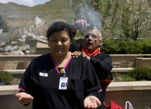 """Kim Raff     The Salt Lake Tribune Ivette Calaway, a health unit coordinator, participates in a smudging ceremony by Native American shaman, Lacee Harris during the """"Blessing of the Hands"""" on the outdoor patio of the Huntsman Cancer Institute in Salt Lake City on May 6, 2013. The event gathered a diverse group of spiritual care providers to bless hospital caregivers, employees  and patrons."""