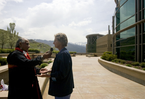 """Kim Raff     The Salt Lake Tribune (right) Cathy Hiatt, a registered nurse, participates in a smudging ceremony by Native American shaman, Lacee Harris during the """"Blessing of the Hands"""" on the outdoor patio of the Huntsman Cancer Institute in Salt Lake City on May 6, 2013. The event gathered a diverse group of spiritual care providers to bless hospital caregivers, employees  and patrons."""