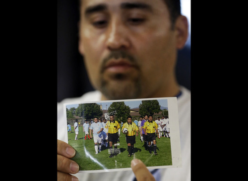 In this Thursday, May 2, 2013 file photo, Jose Lopez points to an undated photo of Ricardo Portillo, center, his brother-in-law, following a news conference, at Intermountain Medical Center, in Murray, Utah. Portillo, a 46-year-old soccer referee who was punched by a teenage player during a game and later slipped into a coma died Saturday night, May 4, 2013, police said. (AP Photo/Rick Bowmer, File)