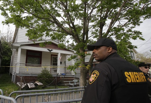 A sheriff deputy stands outside a house where three women escaped Tuesday, May 7, 2013, in Cleveland. Three women who went missing separately about a decade ago were found in the home Monday just south of downtown and likely had been tied up during years of captivity, said police, who arrested three brothers. (AP Photo/Tony Dejak)