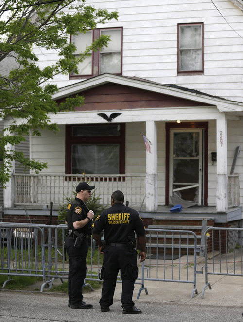 Sheriff deputies stand outside a house in Cleveland Tuesday, May 7, 2013, the day after three women who vanished a decade ago were found there. Amanda Berry, Gina DeJesus and Michelle Knight, who went missing separately about a decade ago, were found in the home just south of downtown Cleveland and likely had been tied up during years of captivity, said police, who arrested three brothers. (AP Photo/Tony Dejak)