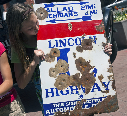 Chris Detrick  |  The Salt Lake Tribune Hawthorne Elementary School fifth-grader Cheyenne Thorsen holds a bullet-riddled Lincoln Highway sign at the Sugarhouse Monument Tuesday May 7, 2013. Students from Hawthorne Elementary School and members of the Utah Lincoln Highway Association placed a historic Lincoln Highway marker at the Sugarhouse Monument to celebrate what was the first U.S. transcontinental highway going through the area.