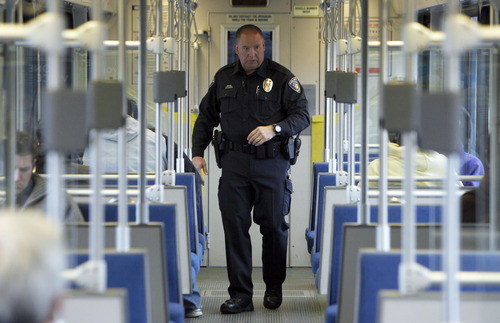 Francisco Kjolseth  |  Tribune file photo     Utah Transit Authority officer Lloyd Davis, a former Layton city officer, rides the TRAX line on the way to the University of Utah. The UTA is looking at alternatives to running its own police department, perhaps saving some on the $5.8 million cost.