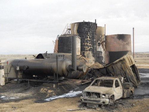 A burned truck sits next to an oil well that exploded May 7, 2013, in Uintah County, killing one man and injuring two others. Photo courtesy Uintah County Sheriff's Office.