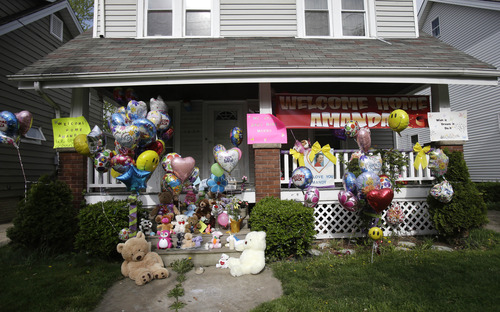 The front porch of Amanda Berry's home is decorated with balloons and signs on Wednesday, May 8, 2013, in Cleveland. Berry, 27, Michelle Knight, 32, and Gina DeJesus, had apparently been held captive in a house since their teens or early 20s, police said. (AP Photo/Tony Dejak)
