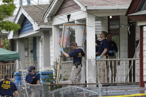 Members of the FBI evidence response team carry out the front screen door from a house Tuesday, May 7, 2013, where three women were held, in Cleveland. Three women who disappeared a decade ago were found safe Monday, and police arrested three brothers accused of holding the victims against their will. (AP Photo/Tony Dejak)