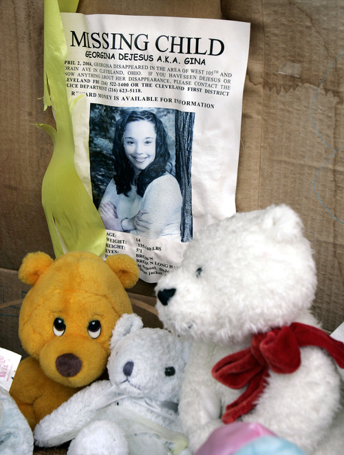 FILE - In this March 3, 2006 file photo, a memorial for Gina DeJesus, who has been missing since April 2, 2004, rests alongside her house in Cleveland. Cleveland police say DeJesus, one of two women who went missing as teenagers about a decade ago has been found alive in a residential area about two miles (three kilometers) south of downtown. (AP Photo/Tony Dejak, File)