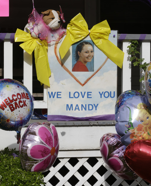 A sign and balloons hang from the front porch of the home of Amanda Berry, Wednesday, May 8, 2013, in Cleveland. Berry, 27, Michelle Knight, 32, and Gina DeJesus,  had apparently been held captive in a house since their teens or early 20s, police said. (AP Photo/Tony Dejak)