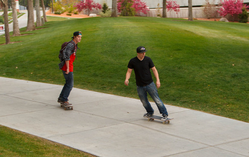 Trent Nelson  |  The Salt Lake Tribune A pair of skateboarders ride through the University of Utah campus in Salt Lake City, Tuesday May 7, 2013. The university is considering a ban on skateboarding.