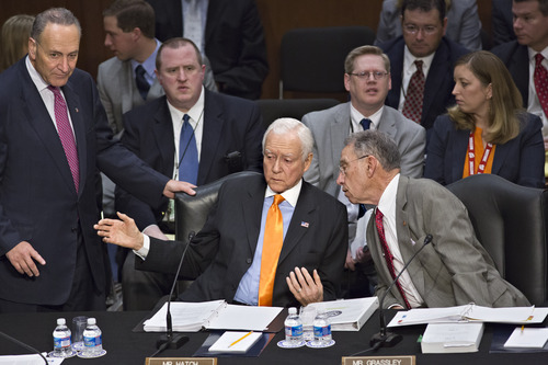 From left, Sen. Chuck Schumer, D-N.Y., standing, Sen. Orrin G. Hatch, R-Utah, and Sen. Chuck Grassley, R-Iowa, confer as the Senate Judiciary Committee meets on immigration reform on Capitol Hill in Washington, Thursday, May 9, 2013. A bill to enact dramatic changes to the nation's immigration system and put some 11 million immigrants here illegally on a path to citizenship is facing its first congressional test as the Senate Judiciary Committee begins considering proposed changes to the 844-page legislation.  (AP Photo/J. Scott Applewhite)