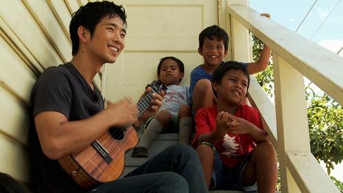 Courtesy photo Jake Shimabukuro visits with children in his old neighborhood in Hawaii.