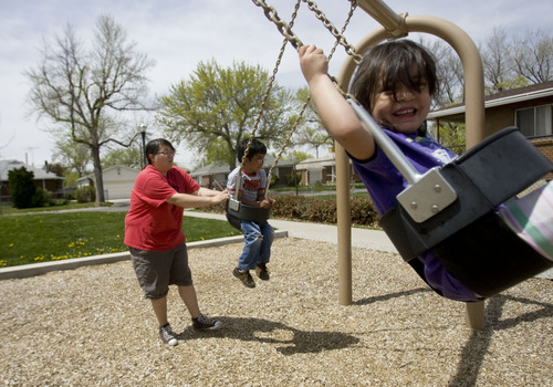Kim Raff  |  The Salt Lake Tribune Isaiah, center, and Isabella Montoya, right, are pushed on the swings by their aunt Michelle Enriquez at Joseph F. Steenblik Park in the Rose Park neighborhood in Salt Lake City.