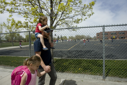 Kim Raff  |  The Salt Lake Tribune Jeremy and (top) Gia Harris pick up (left) Maddie Harris from Rose Park Elementary at the end of the school day in Salt Lake City on April 29, 2013.
