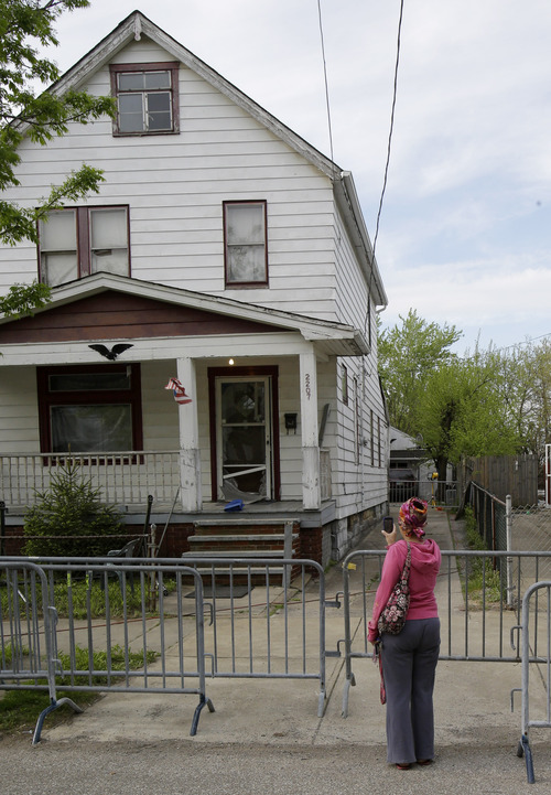 Brittany Moore uses her cell phone to snap pictures of a house where three women escaped Tuesday, May 7, 2013, in Cleveland. Amanda Berry, Gina DeJesus and Michelle Knight, who went missing separately about a decade ago, were found Monday in the home just south of downtown Cleveland and likely had been tied up during years of captivity, said police, who arrested three brothers. (AP Photo/Tony Dejak)
