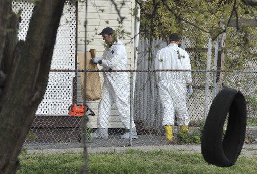 A member of the FBI evidence response team carries out a bag after searching a house near the home where three women were held Wednesday, May 8, 2013, in Cleveland. Amanda Berry, 27, Michelle Knight, 32, and Gina DeJesus, about 23, had apparently been held captive in the house nearby since their teens or early 20s, police said. (AP Photo/Roadell Hickman)