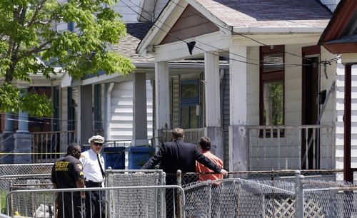 Law enforcement officers talk in front of the house where three women missing for about a decade were found alive, in Cleveland,  Thursday, May 9, 2013.  Ariel Castro was charged with kidnapping and rape while his brothers, Pedro and Onil Castro, were arrested and cleared without charges. (AP Photo/David Duprey)