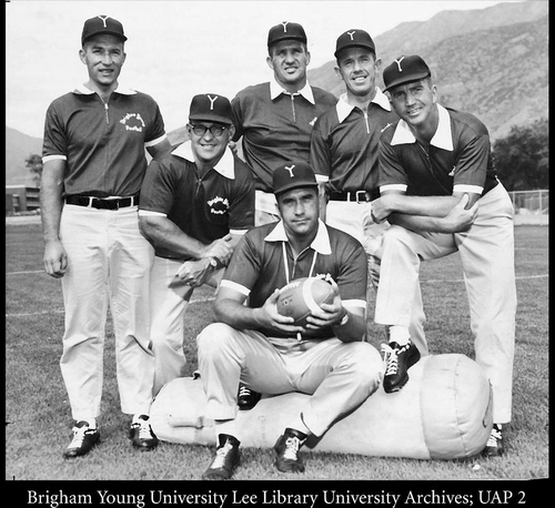 The football coaching staff at BYU in 1960 consisted of Head Coach Tally Stevens (seated); Chris Apostol, left; Owen Dixon, Hal Mitchell, Glen Tuckett, and Carl Rollins. Stevens was named head coach of the Cougars the year before, succeeding Hal Kopp, and completed a two-year win-loss record of 6-15. He was succeeded by Hal Mitchell, who coached three years (1961-63) with a record of 8-22. Courtesy of BYU