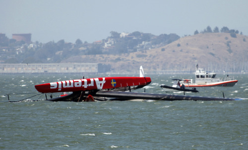 The overturned Artemis Racing AC72 catamaran, an America's Cup entry from Sweden, is towed past Treasure Island after the boat capsized during training in San Francisco Bay on Thursday, May 9, 2013, in San Francisco, Calif. (AP Photo/San Jose Mercury News, Karl Mondon)  MAGS OUT; NO SALES, MADATORY CREDIT BAY AREA NEWSPAPERS