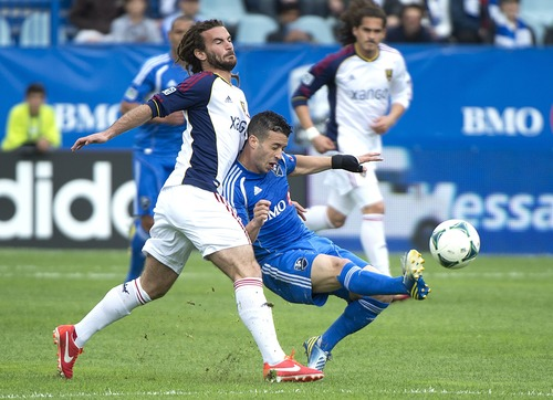 Montreal Impact's Felipe Martins, right, kicks the ball as Real Salt Lake's Kyle Beckerman defends during the first half of an MLS soccer game in Montreal, Saturday, May 11, 2013. (AP Photo/The Canadian Press, Graham Hughes)