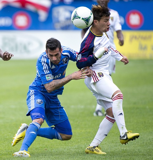Montreal Impact's Andres Romero, left, tackles Real Salt Lake's Sebastien Velasquez during the second half of an MLS soccer game in Montreal, Saturday, May 11, 2013. (AP Photo/The Canadian Press, Graham Hughes)