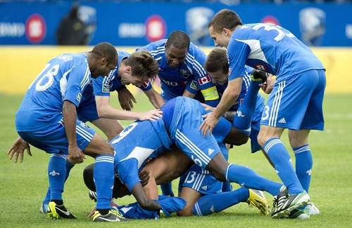 Montreal Impact players celebrate after Matteo Ferrari, bottom, scored an injury time goal against Real Salt Lake in an MLS soccer game in Montreal, Saturday, May 11, 2013. (AP Photo/The Canadian Press, Graham Hughes)