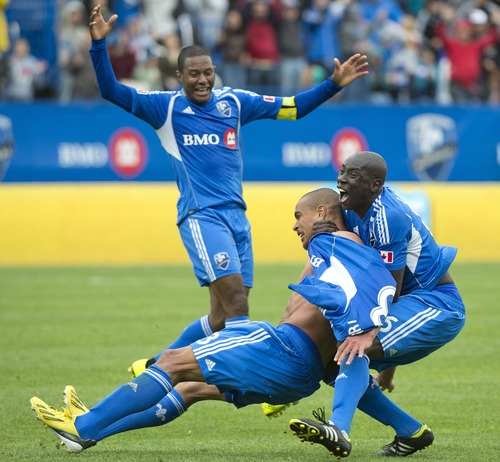 Montreal Impact's Matteo Ferrari, bottom, celebrates with teammates Patrice Bernier and Hassoun Camara, right, after scoring an injury time goal against Real Salt Lake in an MLS soccer game in Montreal, Saturday, May 11, 2013. (AP Photo/The Canadian Press, Graham Hughes)