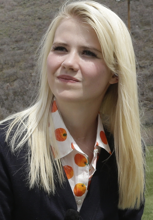"""FILE - In this Tuesday, May 7, 2013 file photo, Elizabeth Smart prepares for an interview, in Park City, Utah. Smart said she's elated to hear about three Cleveland women who escaped Monday, May 6, after they disappeared a decade ago. """"First of all, I'd make sure these young women know that nothing that happened to them is their fault,"""" Smart recently told People magazine. Smart was kidnapped from her bedroom in Salt Lake City when she was 14. She was freed nine months later when she was found walking with her captor on a suburban street in March 2003.  (AP Photo/Rick Bowmer, File)"""