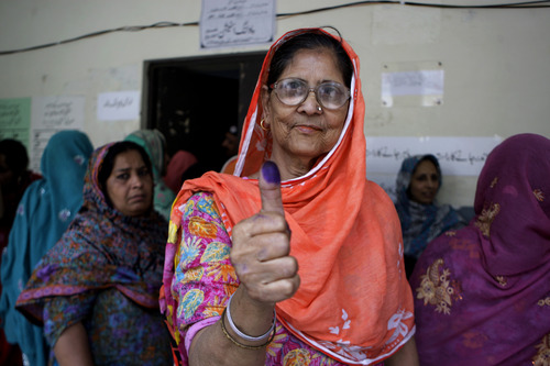 A Pakistani woman shows her ink-stained thumb after casting her ballot at a polling station in Lahore, Pakistan, Saturday, May 11, 2013. Defying the danger of militant attacks, Pakistanis streamed to the polls Saturday for a historic vote pitting a former cricket star against a two-time prime minister and an unpopular incumbent. But bombings that killed and wounded dozens underlined the risks many people took just casting their ballots. (AP Photo/K.M. Chaudary)