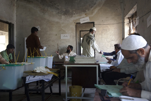 Pakistanis receive their ballot papers before at a polling station in Lahore, Pakistan, Saturday, May 11, 2013. Defying the danger of militant attacks, Pakistanis streamed to the polls Saturday for a historic vote pitting a former cricket star against a two-time prime minister and an unpopular incumbent. But attacks that killed and wounded dozens of people underlined the risks many people took just casting their ballots. (AP Photo/Rebecca Conway)