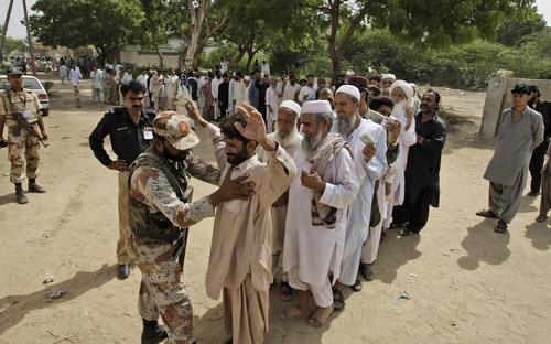 A Pakistani paramilitary soldier checks voters before they enter a polling station to cast their ballots, in Karachi, Pakistan, Saturday, May 11, 2013.  Defying the danger of militant attacks, Pakistanis streamed to the polls Saturday for a historic vote pitting a former cricket star against a two-time prime minister and an unpopular incumbent. But bombings that killed at least ten people and wounded dozens more underlined the risks many people took just casting their ballots. (AP Photo/Fareed Khan)