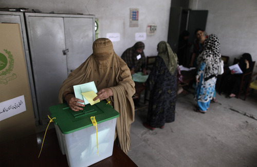 A Pakistani woman casts her ballot at a polling station on the outskirts of Islamabad, Pakistan, Saturday, May 11, 2013. Pakistanis streamed to the polls Saturday to vote in a historic election pitting a cricket star-turned-politician against an unpopular incumbent and a two-time prime minister, but twin bombings killing nine people and wounding dozens underlined the dangers voters face. (AP Photo/Muhammed Muheisen)