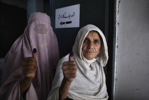 Pakistani women show their election ink-stained thumbs after casting their ballots at a polling station on the outskirts of Islamabad, Pakistan, Saturday, May 11, 2013. Pakistanis streamed to the polls Saturday to vote in a historic election pitting a cricket star-turned-politician against an unpopular incumbent and a two-time prime minister, but twin bombings killing nine people and wounding dozens underlined the dangers voters face. (AP Photo/Muhammed Muheisen)