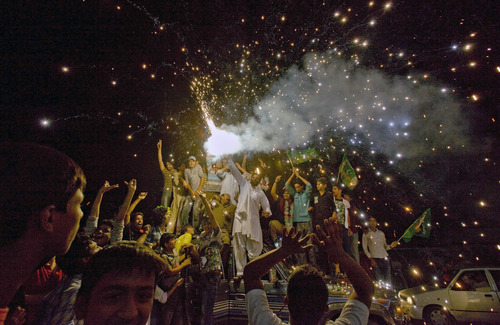 Supporters of Pakistan Muslim League-N party release firework to celebrate their party victory in the parliamentary election at outside the party's headquarter in Lahore, Pakistan, Sunday, May 12, 2013. Former Pakistani Prime Minister Nawaz Sharif looked set Sunday to return to power for a third term, with an overwhelming election tally that just weeks ago seemed out of reach for a man who had been ousted by a coup and was exiled abroad before clawing his way back as an opposition leader. (AP Photo/Anjum Naveed)
