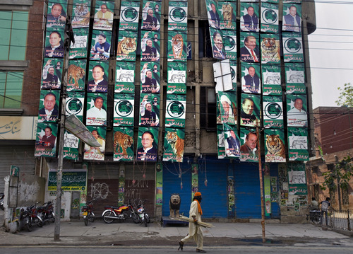 A Pakistani man walks past posters of former prime minister and Pakistan Muslim League-N party chief Nawaz Sharif, displayed on his party's office building in Lahore, Pakistan, Sunday, May 12, 2013. Sharif declared victory following a historic election marred by violence Saturday, a remarkable comeback for a leader once toppled in a military coup and sent into exile. (AP Photo/Anjum Naveed)