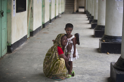 A Bangladeshi woman reacts holding her son's daughter after her son's body was found after the April 24 garment factory building collapse in Savar, near Dhaka, Bangladesh, Sunday, May 12, 2013. Search teams resumed their rain-interrupted work Sunday as the death toll from the collapse continued to climb past 1,100. (AP Photo/Ismail Ferdous)